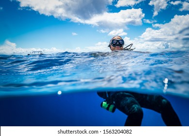 Scuba Diver Girl floating on Ocean Surface on a sunny Day