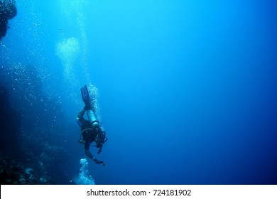 Scuba diver going deep in the ocean taking a selfie. Action and adventure sports background.
