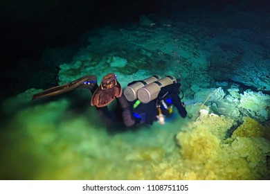 Scuba diver and halocline in the underwater cave. Halocline - optical effect of mixing fresh and sea water. Scuba diving in the cave.