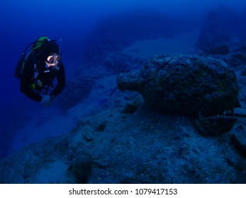 scuba diver looking at an ancient amphora underwater