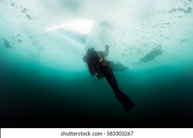 Scuba diver looking at ice hole, while ice diving