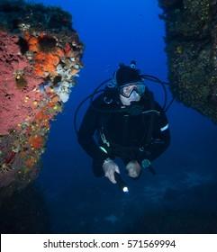 Scuba diver looking into underwater cave.