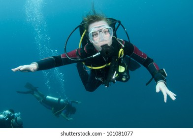 scuba diver looks at camera while swimming in Thailand