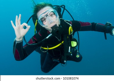 scuba diver makes OK sign underwater