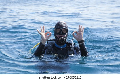 Scuba diver makes the ok sign with two hands