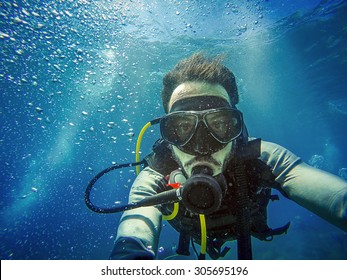 Scuba diver man swimming on a blue water sea looking at camera