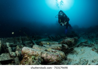 scuba diver over the wooden wreck of a diving boat with tanks in