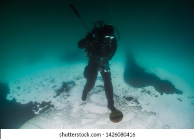 Scuba diver plays football under the ice.