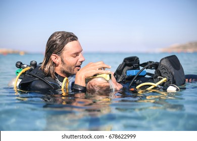 Scuba diver rescuing a girl who doesn't feel good