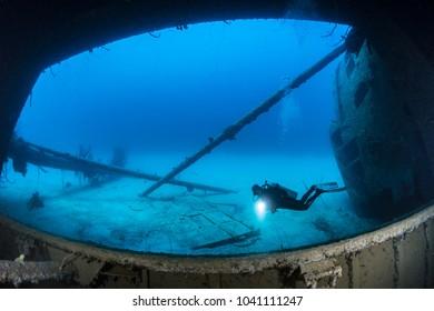 Scuba Diver shining light over the Hilma Hooker Wreck, Bonaire