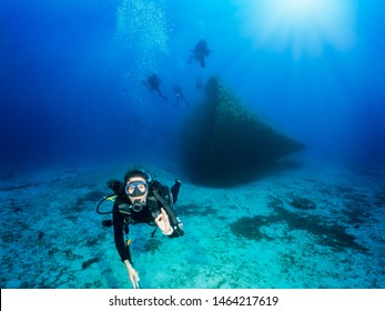 Scuba diver shows the OK sign under water during a deep wreck dive in the blue, Aegean Sea in Greece