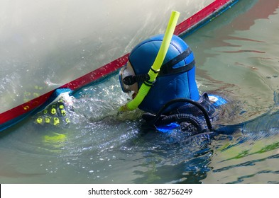 Scuba diver with snorkel and aqualung tank is cleaning a boat hull with a scrubbing pad removing all organic growth so the hull is smooth & clean resulting in higher speeds and better fuel efficiency
