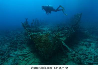 Scuba diver swim over very old ship wreck
