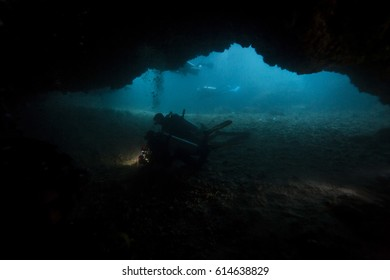 Scuba diver swim through a cave, Malapascua.