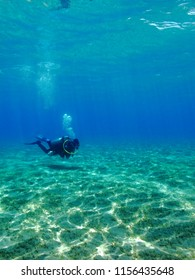 Scuba diver swimming in the blue sea. Shallow ocean and underwater diver. Tourist in the shallow water. Scuba diver seascape.