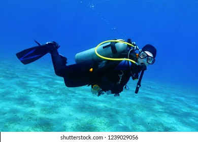 Scuba diver swimming in the shallow blue sea with sandy seabed. Diver exploring the blue water. Underwater photography, portrait of the scuba diver.