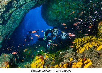 SCUBA diver swimming through an underwater cave in the Mergui Archipelago, Myanmar