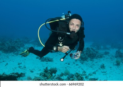 scuba diver takes her mask off underwater