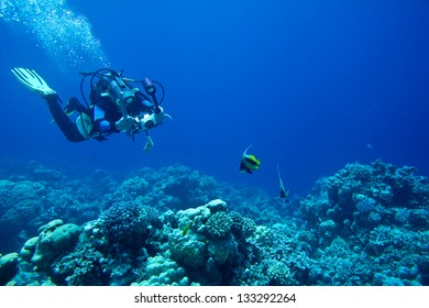 Scuba diver taking Photo/Video at coral reef in the Red Sea, Egypt