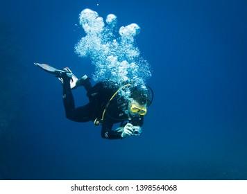 Scuba diver taking underwater photo in deep blue water
