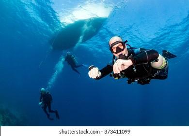 SCUBA diver in a technical sidemount configuration underneath a dive boat