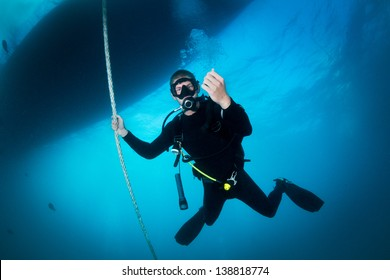 Scuba Diver underwater of the big blue sea making safety stop after a dive holding the line underneath the boat at depth from 3 to 6 meters to release the nitrogen saturated in his body after a dive.