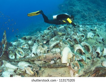 Scuba diver underwater exploring wreckage from a shipwreck on a tropical reef