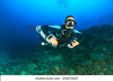 SCUBA diver using twin sidemount tanks deep underwater
