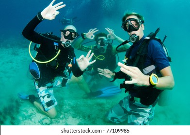 Scuba Divers all give OK signs and are very happy