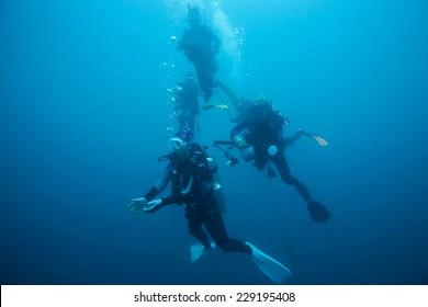 scuba divers descending on a descent line