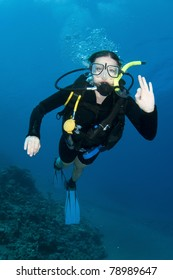 Scuba divers enjoy the dive and make OK sign