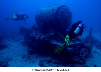 Scuba divers explore a sunken steam engine in the wreck of the S. S. Thistlegorm in the Red Sea, Egypt