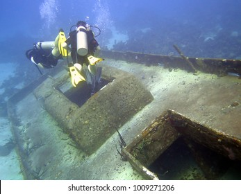 Scuba divers explore the wreck of a sunken boat.