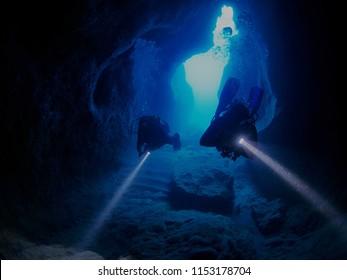 scuba divers exploring caves underwater cave diving