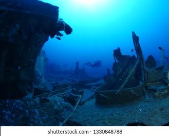 scuba divers exploring and enjoying ship wreck underwater