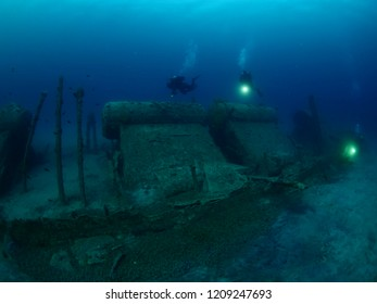 scuba divers exploring and filming ship wreck from world war 1