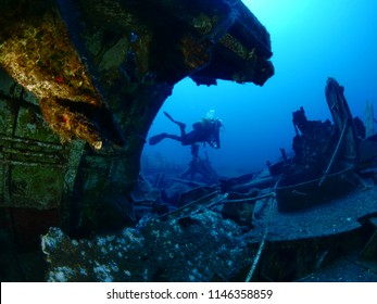 scuba divers exploring ship wreck underwater diving holiday