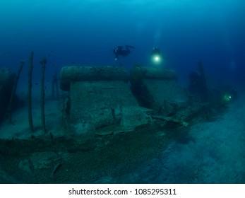 scuba divers exploring world war one ship wreck underwater