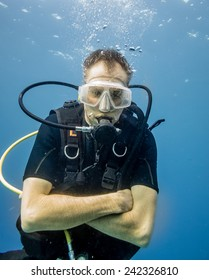 Scuba divers feels chilly, because he is only wearing a short sleeve wetsuit (shorty)