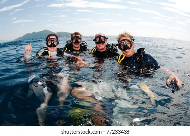 Scuba Divers happy together on surface before diving