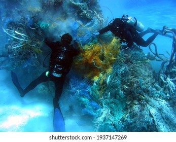 Scuba divers removing derelict net from reef. This debris pile was an agglomeration of a number of nets that had probably been swept together in the North Pacific Gyre. Northwest Hawaiian Islands