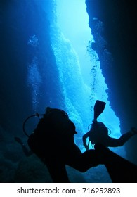 Scuba divers in silhouette with air bubbles in a limestone fissure