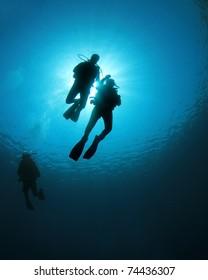 Scuba Divers swim together in blue ocean, silhouette against sunburst