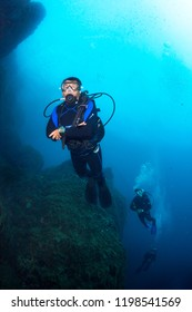 Scuba divers underwater in the deep blue ocean and backlight sun.