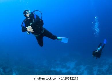 Scuba divers underwater in the deep blue ocean.