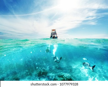 Scuba divers underwater and fishing tour boat above the Caribbean Sea in Cozumel, Mexico