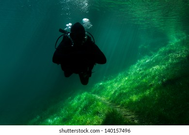 Scuba Diving Alps lake. Cold crystal clear, emerald water with sun-rays. Austria. Sunken Park.