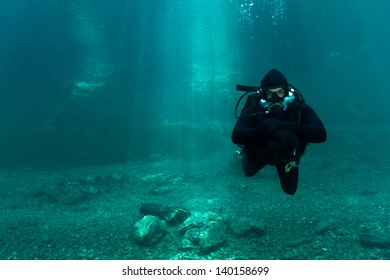 Scuba Diving Alps lake. Cold blue crystal clear water with sun-rays.Austria.