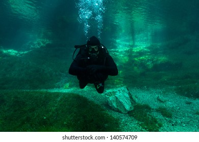 Scuba Diving Alps lake. Cold emerald, crystal clear water with sun-rays. Gruner See, Austria. Sunken Park.
