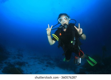 Scuba diving exploring coral reef in Similan Islands Thailand